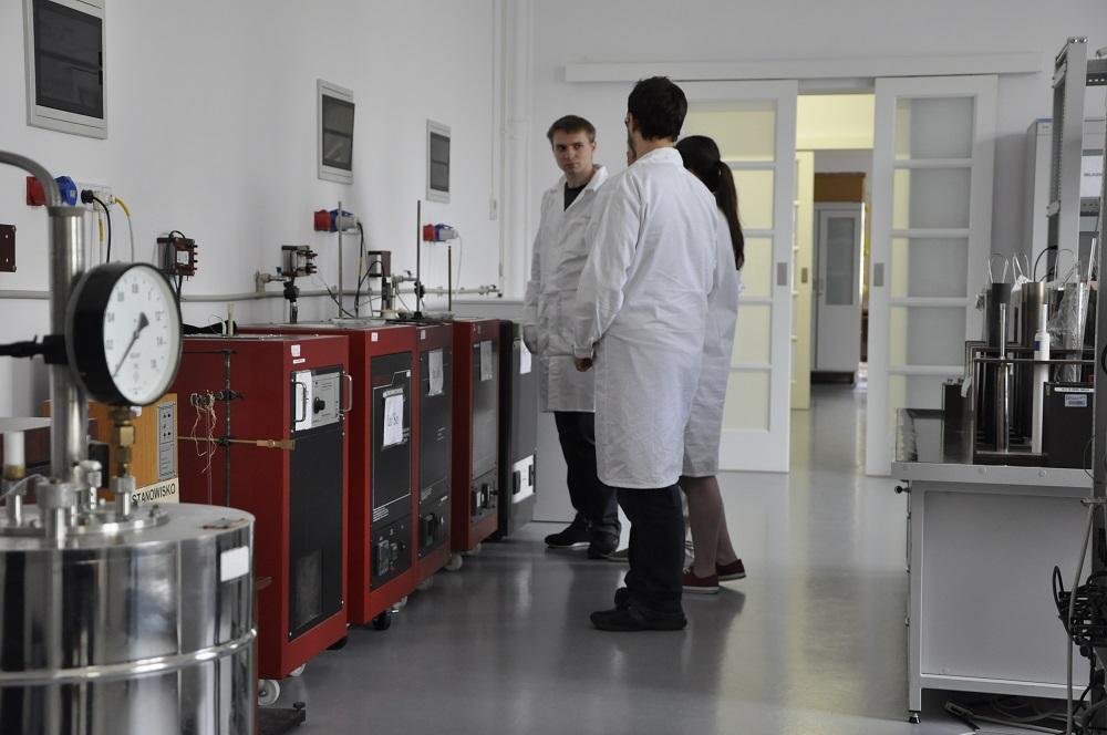 Na zdjęciu kilkoro pracowników laboratorium w fartuchach stoi w pobliżu stanowiska wzorca państwowego temperatury w laboratorium termometrii.